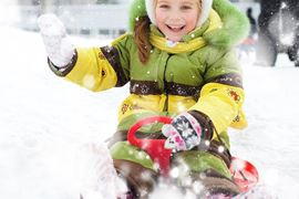 Europe Holidays -Finland, Lapland - Happy child on sledge in winter
